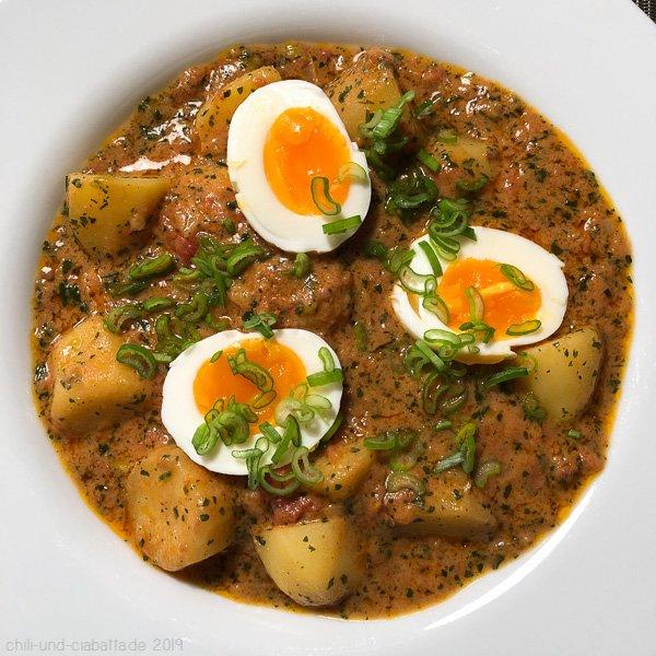 Gelbes Kartoffel-Curry mit Tomaten und wachsweichen Eiern